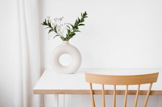 Stylish vase with flowers on table