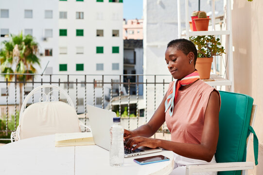 Woman working from home on her balcony