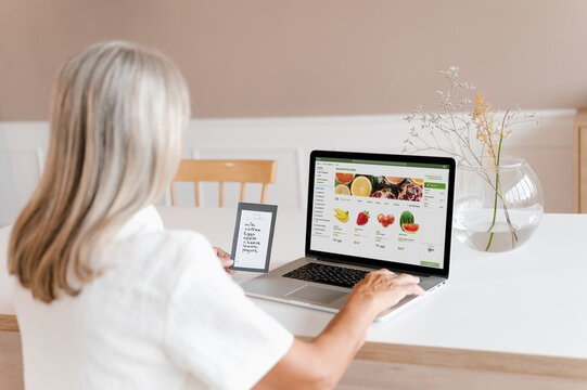 Woman making online order of fruits on laptop