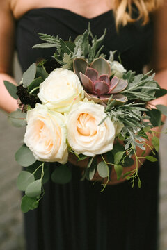 bridesmaid with cute black dress and flower bouquet