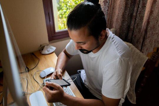 South Asain man looking at his phone.