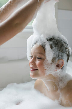 Happy Child Taking a Bubble Bath with Suds