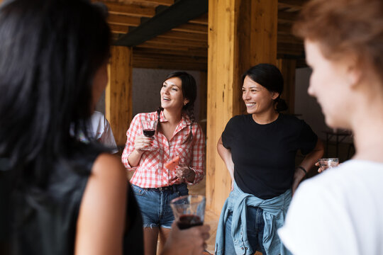 Happy women chatting during wine tasting in cellar
