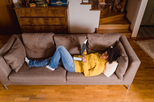 Black woman reading a book on the sofa at home