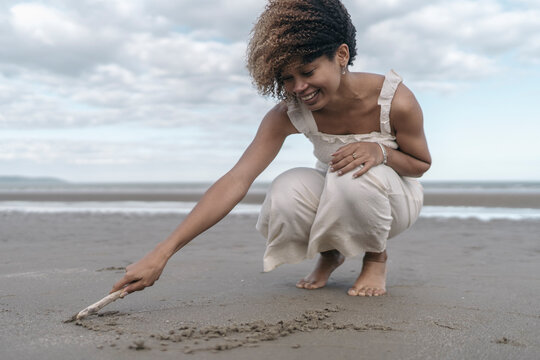Young Black Woman Drawing on the Sand
