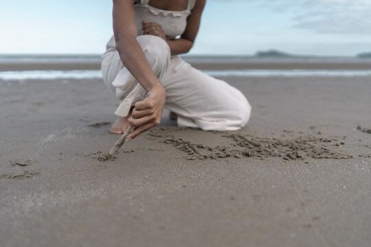 Anonymous Woman Drawing on the Sand