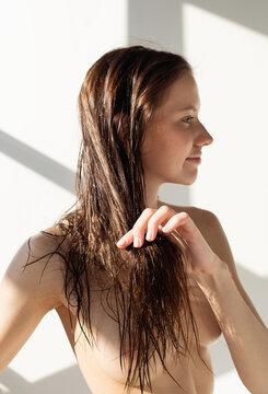 Naked woman touching wet hair