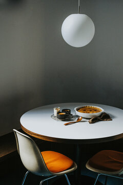 Creme brulee cooling down on a round table with two chairs and white light bulb