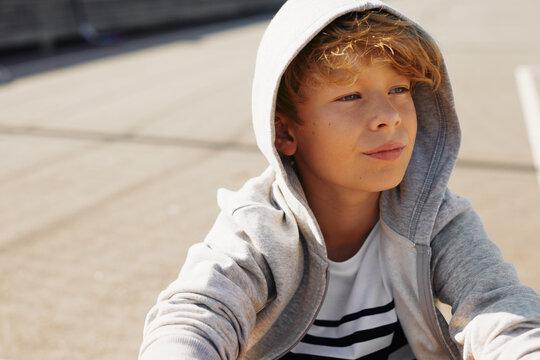 Boy sitting outside on a basketball court