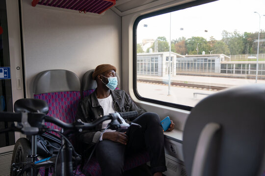 Man Wearing Mask With Bicycle In Train Station