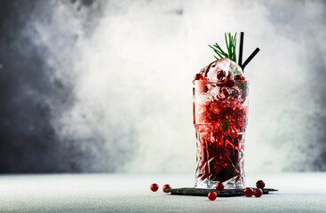 Cranberry cocktail with ice, rosemary and berries in highball glass, gray background, copy space