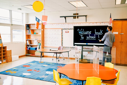 """Elementary school teacher writing """" Welcome back to school!"""" on a digital board, during Covid-19 pandemic."""