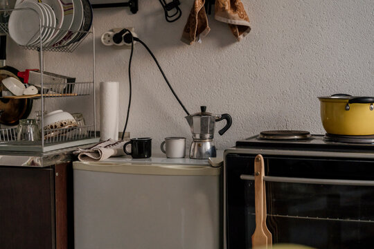 Rustic kitchen with cooking pot on stove and drying plates