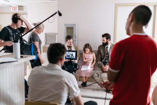 A film crew watches as three actors perform a scene