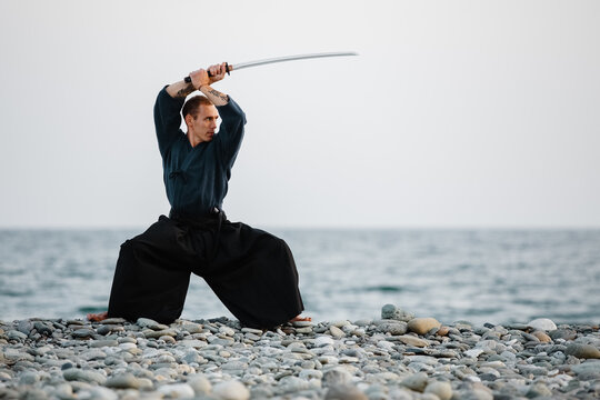 Samurai practicing with sword on seashore