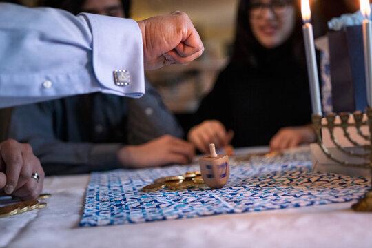 Hanukkah: Father Spins Dreidel During Game
