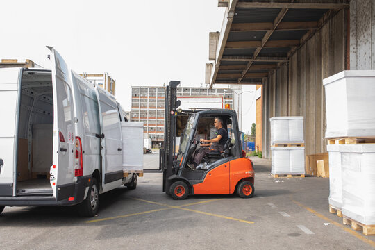 The worker transports freight into a van using a forklift