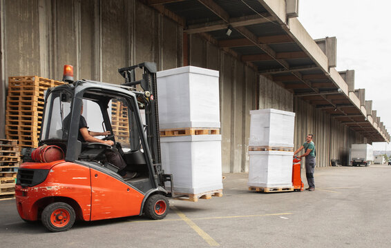 The worker transports freight using a forklift