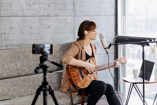 Woman recording video on smartphone and playing guitar