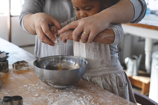 クッキー作りでお母さんと一緒に卵を割る女の子