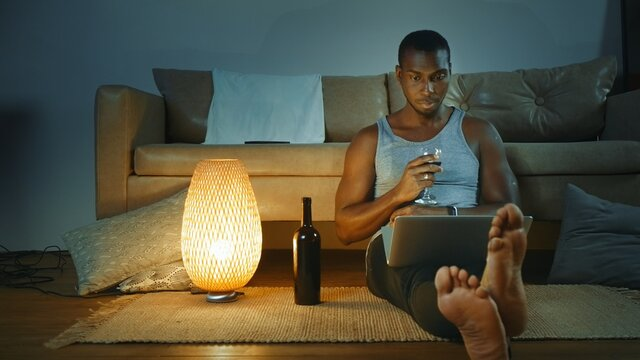 Young African American man using laptop, drinking red wine from glass, looking at the screen. The concept of watching a movie, video.