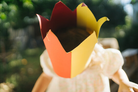 Cute little girl in paper crown playing outside