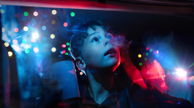 Young boy looking out the car window at christmas lights in amazement