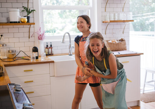 Two sisters having fun baking cookies together in a modern kitch