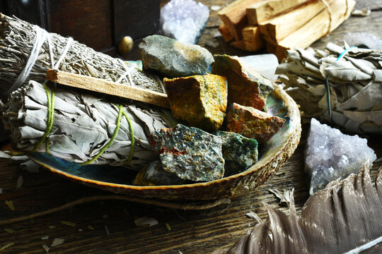 A close up image of sage smudge sticks and healing crystals in an abalone shell.