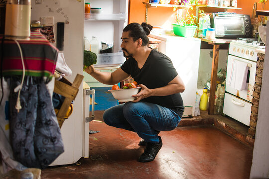 Man taking a broccoli out of the fridge