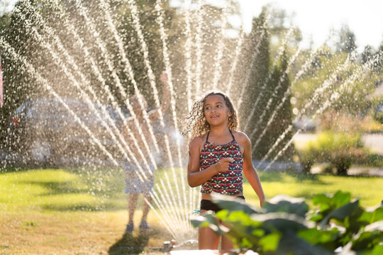 Mixed race girl with curly hair runs through sprinkler on summer day