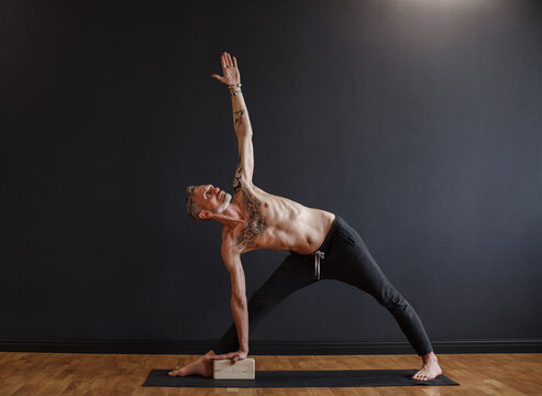 Flexible mature man practicing triangle pose