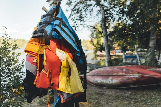 Life jackets on a pole by a lake