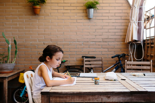 Kid doing homework in home terrace