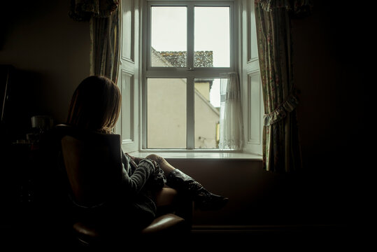 Young woman sitting in front of a window