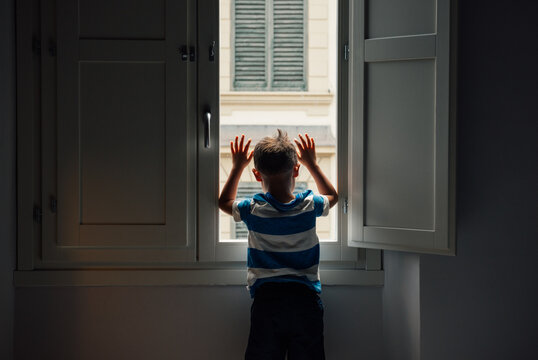 Little boy stuck indoors and looking out his second floor window.