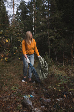 Woman collects plastic litter in the forest