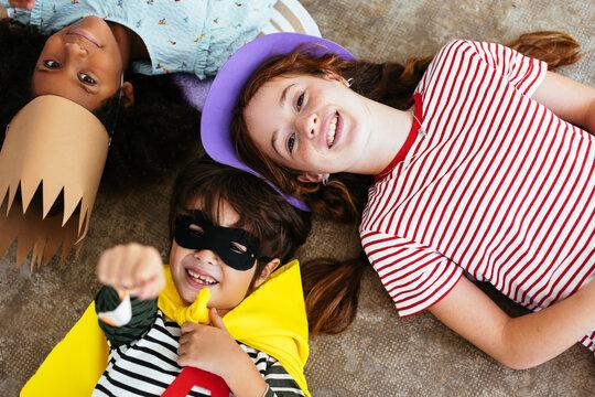 Happy multiethnic friends in Halloween costumes on floor