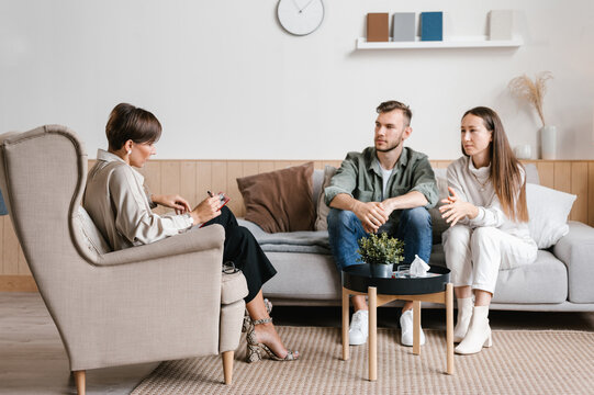 Young couple and female realtor talking in modern apartment