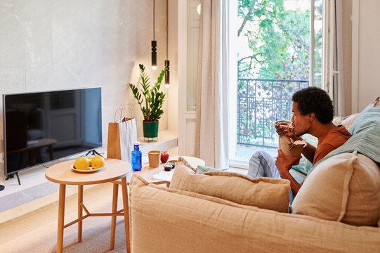 Man eating takeaway food in his living room