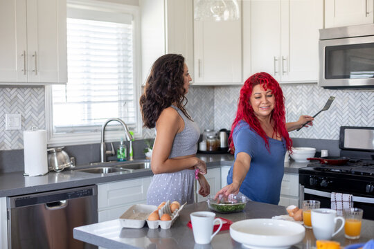 Mother Cooks Eggs For Daughter For Brunch