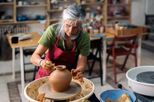Woman Making Pottery On Spinning Wheel