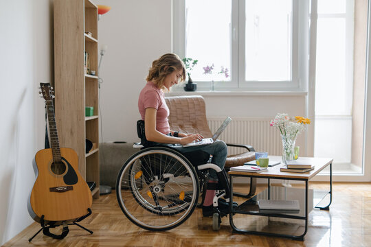 Young woman in a wheelchair working from home on her laptop