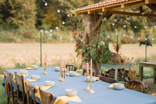 Table with linen tablecloth candles and bouquets located near pool during wedding