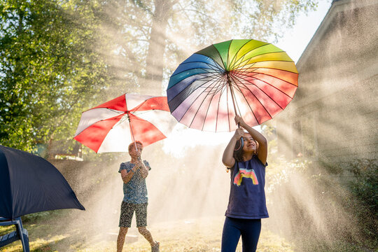 Girl with rainbow umbrella in water mist
