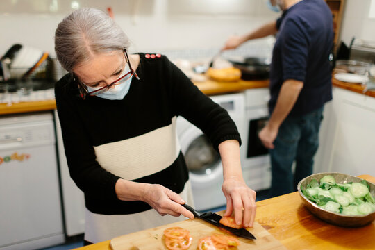 Elderly woman wearing a face mask preparing a salad in the kitchen while a man cooks in the background.