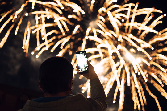 Young man photographing fireworks culmination using smartphone