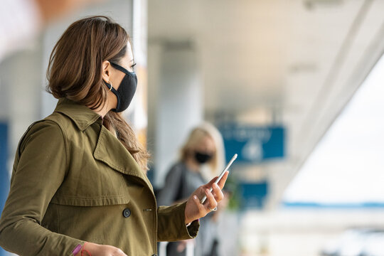Travel: Woman Checks Rideshare App While Waiting For Ride