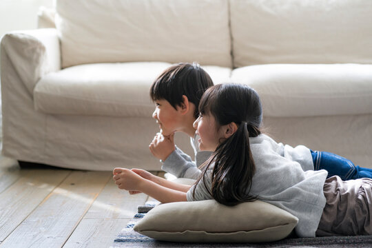 リビングの床に寝転ぶ日本人の男の子と女の子