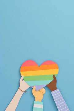 Many hands holding the rainbow heart of LGBT flag